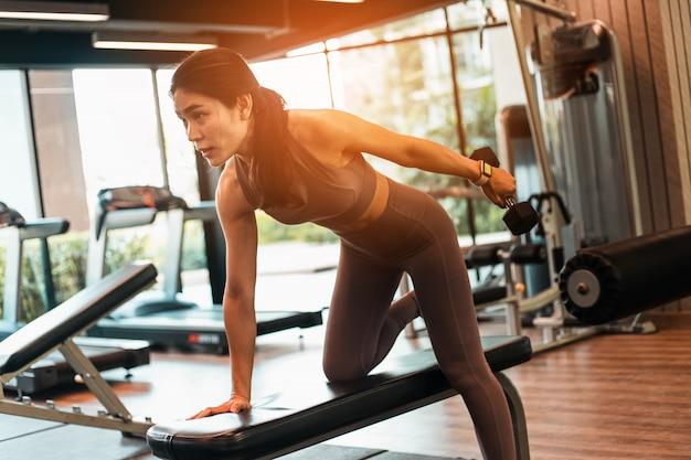 Jonge slanke vrouw die sportkleding draagt die oefening met gewichten in gymnastiek doet.