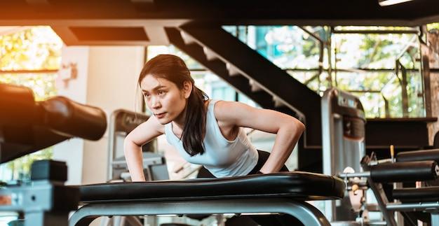 Jonge slanke vrouw doet push-ups op de stoel van de oefening in de fitnessruimte