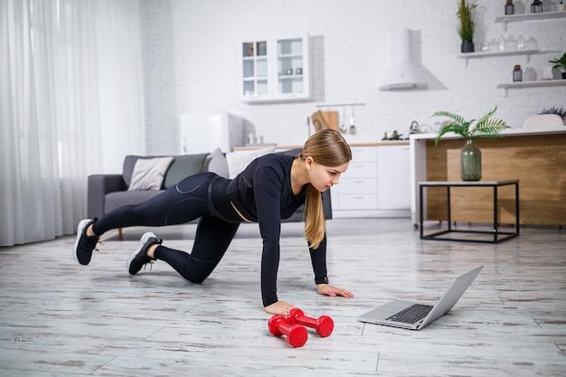 Jonge slanke vrouw gaat thuis sporten. een mooie sportvrouw met blond haar doet oefeningen en kijkt thuis naar een online training op een laptop. thuis fitnessen tijdens quarantaine.