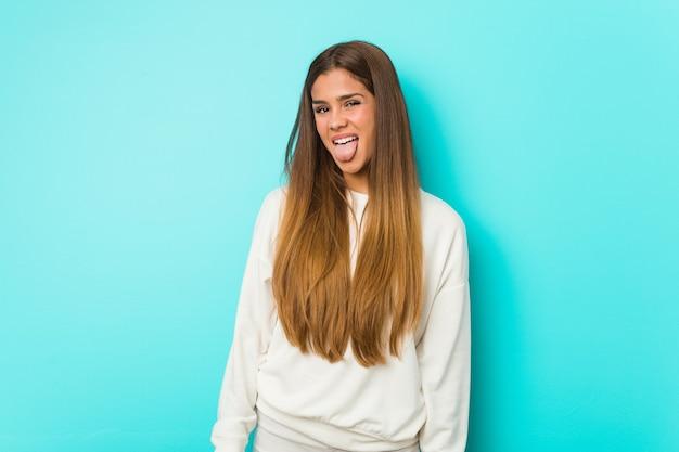 Jonge slanke vrouw grappige en vriendelijke tong uitsteekt.