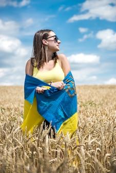 Jonge slanke vrouw in blauw-gele vlag van oekraïne op tarweveld in de zomer
