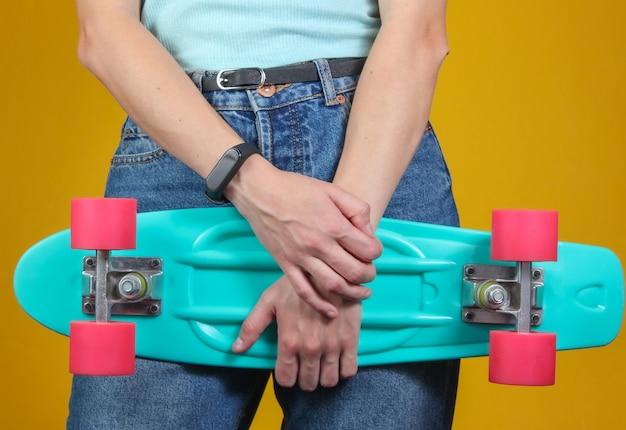 Jonge slanke vrouw in spijkerbroek houdt plastic cruiser board in haar handen op gele achtergrond. hipster-mode voor jongeren. zomerplezier.