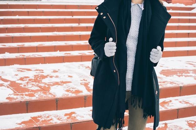 Jonge slanke vrouw in unbuttoned zwarte jas, een grijze trui en handschoenen wandelen langs de besneeuwde rode ladder