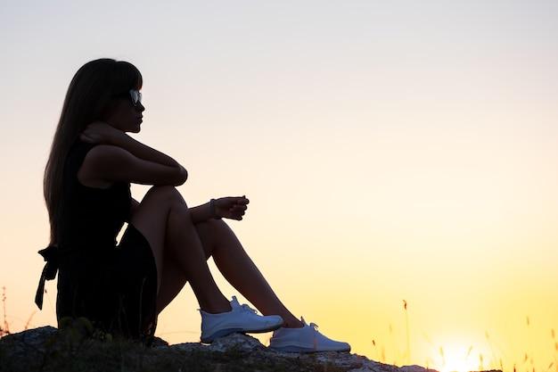 Jonge slanke vrouw in zwarte korte jurk zittend op een rots buiten ontspannen bij zomer zonsondergang. modieuze vrouw genieten van warme avond in de natuur.