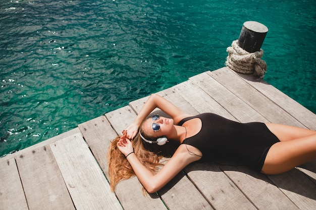 Jonge slanke vrouw liggend op de pier, middellandse zee, azuurblauw water, zonnig, gebruinde huid, luisteren muziek, koptelefoon, zwart zwempak, sexy lichaam, zonnebaden, tropische vakantie, ontspannen, zonnebril