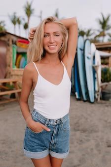 Jonge slanke vrouw met een gebruinde huid gekleed in denim shorts en wit overhemd poseren met opgeheven hand