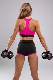 Jonge slanke vrouw met een mooi atletisch lichaam een training met halters