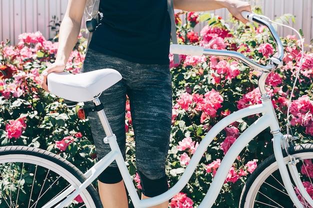 Jonge slanke vrouw staat met een fiets tegen een achtergrond van struiken met rozen