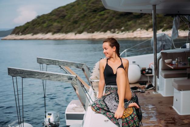 Jonge slanke vrouw zitten in bikini badpak op een jacht en koesteren in de zon