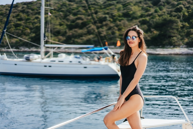 Jonge slanke vrouw zitten in bikini badpak op een jacht in zonnebril en koesteren in de zon