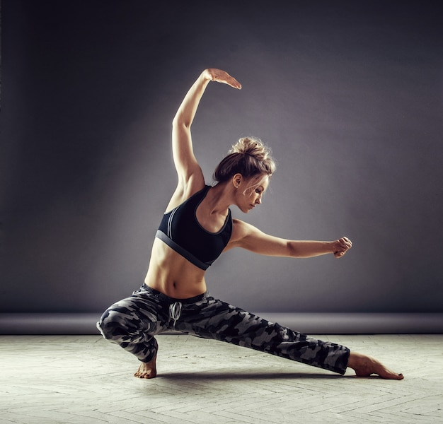 Jonge slanke vrouwendanser in sportkleding springen hoog op muur achtergrond
