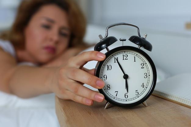 Jonge slaperige vrouw die de wekker probeert uit te schakelen. vroeg in de ochtend wakker worden.