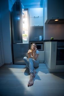 Jonge slaperige vrouw die 's avonds laat op de vloer bij een open koelkast zit