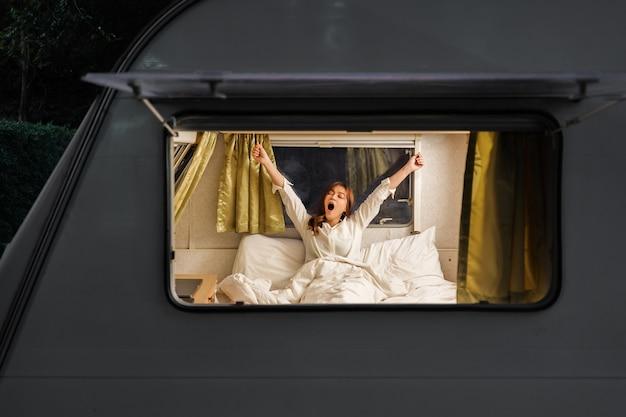 Jonge slaperige vrouw op bed van een camper rv busje camper