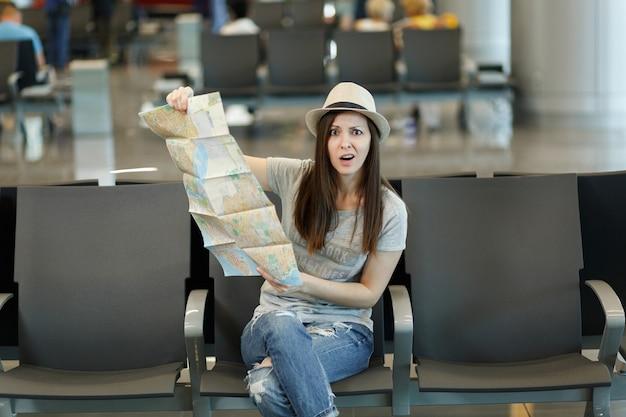Jonge slaphappy reizigerstoeristenvrouw die papieren kaart vasthoudt, route zoekt, wacht in de lobby op de internationale luchthaven