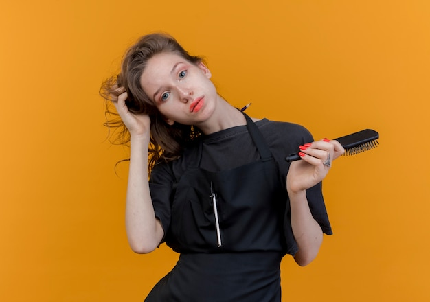 Jonge slavische vrouwelijke kapper die eenvormig draagt ?? die de kam van de cameraholding bekijkt en haar grijpt dat op oranje achtergrond met exemplaarruimte wordt geïsoleerd