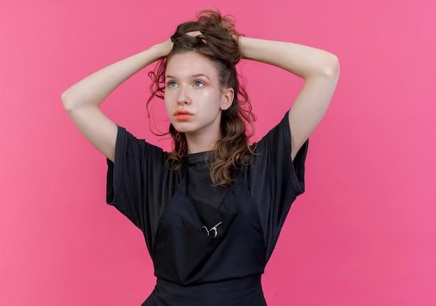 Jonge slavische vrouwelijke kapper die eenvormig draagt ?? kijkt die haar haar grijpt dat op roze achtergrond met exemplaarruimte wordt geïsoleerd