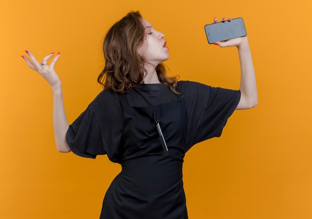 Jonge slavische vrouwelijke kapper die eenvormig zingen draagt ?? die mobiele telefoon als microfoon gebruikt die hand in lucht houden die op oranje achtergrond wordt geïsoleerd