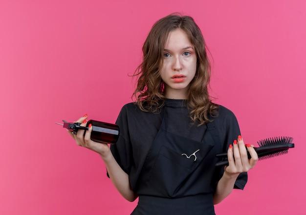 Jonge slavische vrouwelijke kapper die eenvormige kammen en schaar van de holdingsnevelfles draagt ?? die camera bekijkt die op roze achtergrond wordt geïsoleerd