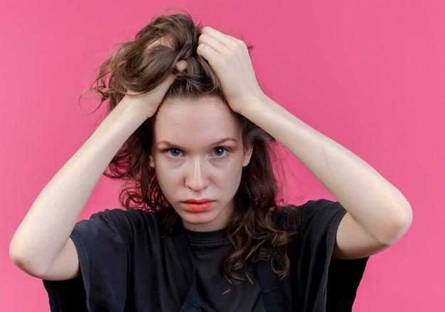 Jonge slavische vrouwelijke kapper die uniform draagt ?? camera kijken en hoofd houden geïsoleerd op roze achtergrond