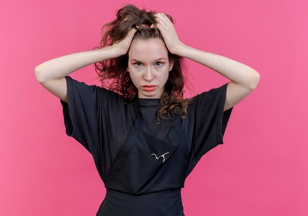 Jonge slavische vrouwelijke kapper dragen uniform camera kijken en hoofd houden geïsoleerd op roze achtergrond