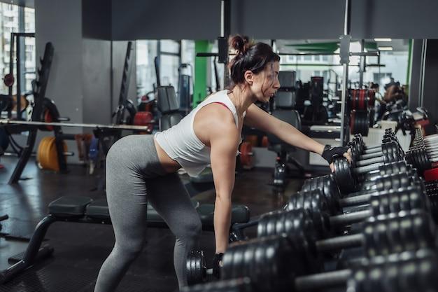 Jonge slim fit fenchin doet een oefening een halter aan een riem trekken, leunend op een rek met halters in de sportschool.