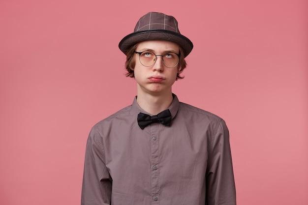 Jonge slim geklede man luistert onoplettend moraliserend van zijn ouders, moe van morele lezing, pufte met zijn wangen rolde met zijn ogen, over roze achtergrond