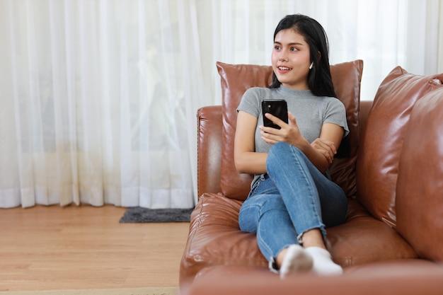 Jonge slimme en actieve aziatische vrouw zittend op de bank in de woonkamer, met behulp van smartphone met blij lachend gezicht