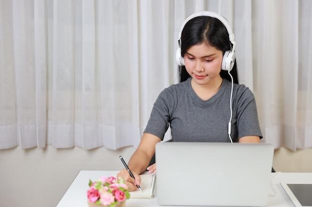 Jonge slimme en actieve aziatische vrouwelijke student zittend aan tafel met headset, computer gebruikend en noteren voor online studeren met blij lachend gezicht (nieuw normaal concept)