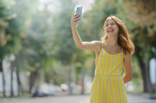 Jonge slimme glimlachende vrouw die een selfie met haar mobiele telefoon neemt.