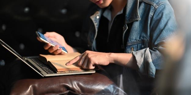 Jonge slimme mens die een smartphone houden terwijl het lezen van een boek en het zitten voor computerlaptop dat het zetten op zijn overlapping over comfortabele laag in woonkamer als achtergrond.