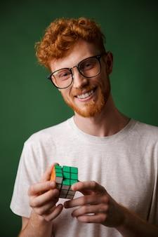 Jonge slimme readgead bebaarde man in glazen, spelen met rubic's kubus