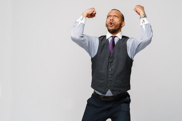 Jonge slimme schreeuwende afro-amerikaanse zakenman die het gebaar van de succeswinst doet.