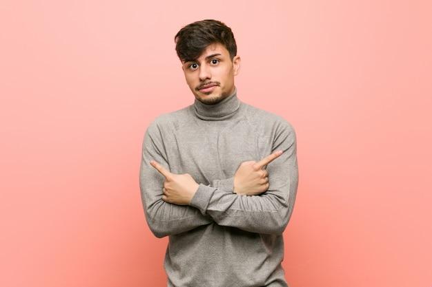 Jonge slimme student man wijst zijwaarts, probeert te kiezen tussen twee opties.