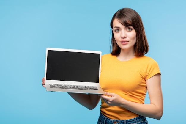 Jonge slimme student met laptop terwijl hij de presentatie van een nieuw project of product voor u maakt