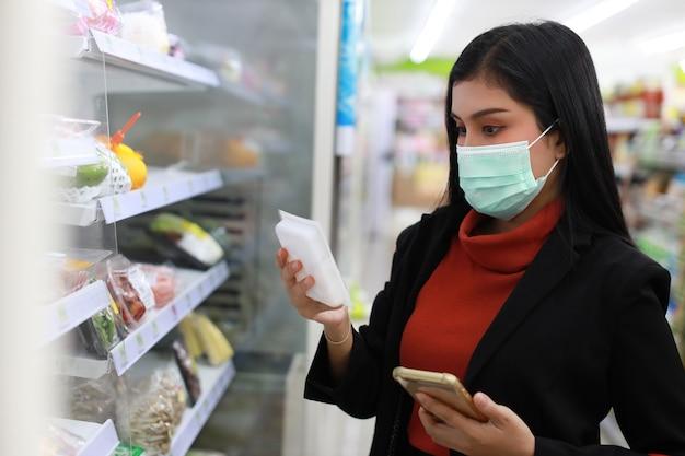 Jonge slimme zakelijke aziatische vrouw die gezichtsmasker draagt die en kruidenierswinkel kijkt kiezen om van plank in supermarktwarenhuis of winkelcentrum te kopen