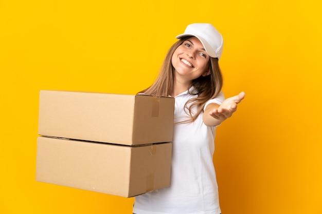 Jonge slowaakse leveringsvrouw die op gele achtergrond wordt geïsoleerd die handen schudden voor het sluiten van een goede overeenkomst