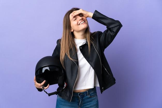 Jonge slowaakse vrouw die een motorhelm houdt die op paarse muur wordt geïsoleerd die veel glimlacht