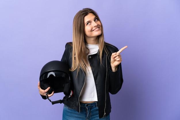 Jonge slowaakse vrouw die een motorhelm houdt die op purpere achtergrond wordt geïsoleerd die een geweldig idee benadrukt