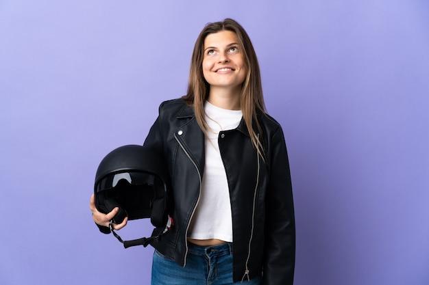 Jonge slowaakse vrouw die een motorhelm houdt die op purpere achtergrond wordt geïsoleerd die een idee denkt terwijl het opzoeken