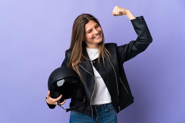 Jonge slowaakse vrouw die een motorhelm houdt die op purpere achtergrond wordt geïsoleerd die een overwinning viert