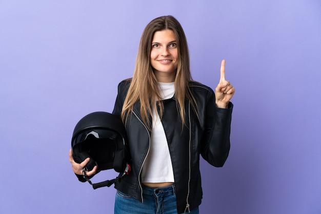 Jonge slowaakse vrouw die een motorhelm houdt die op purpere muur wordt geïsoleerd die een geweldig idee benadrukt