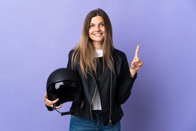Jonge slowaakse vrouw die een motorhelm houdt die op purpere muur wordt geïsoleerd die en een vinger opheft als teken van het beste