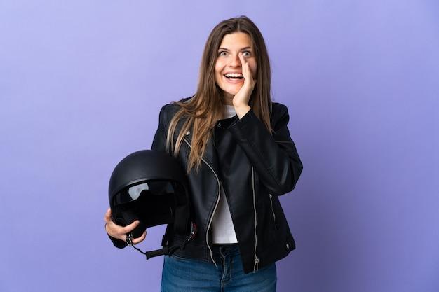 Jonge slowaakse vrouw die een motorhelm houdt die op purpere muur wordt geïsoleerd die met wijd open mond schreeuwt
