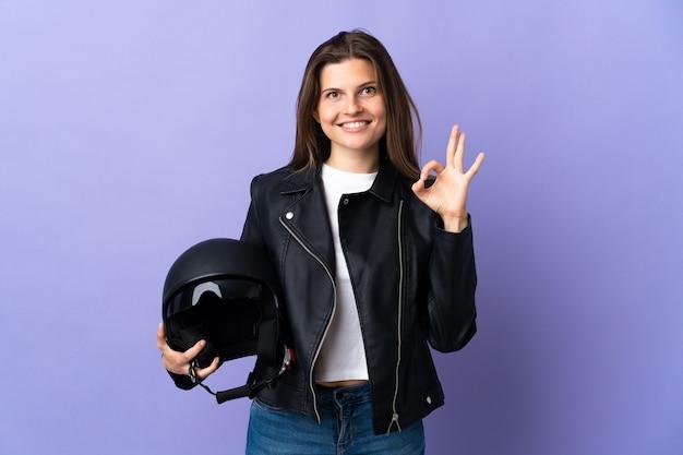 Jonge slowaakse vrouw die een motorhelm houdt die op purpere muur wordt geïsoleerd die ok teken met vingers toont
