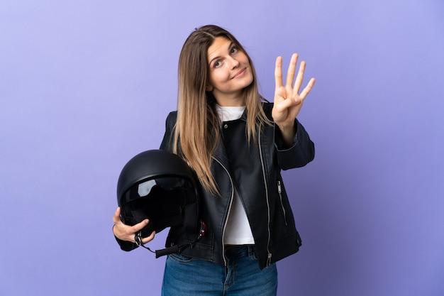 Jonge slowaakse vrouw die een motorhelm houdt die op purpere muur wordt geïsoleerd gelukkig en vier met vingers telt