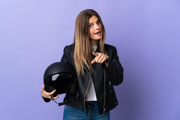 Jonge slowaakse vrouw die een motorhelm houdt die op purpere muur wordt geïsoleerd verrast en wijst naar voren