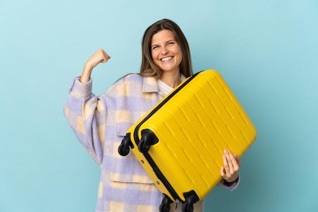 Jonge slowaakse vrouw die op blauwe muur in vakantie met reiskoffer wordt geïsoleerd