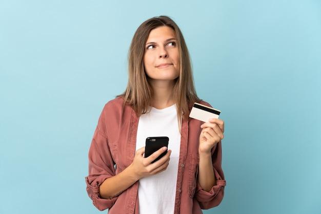 Jonge slowaakse vrouw geïsoleerd kopen met de mobiel met een creditcard tijdens het denken