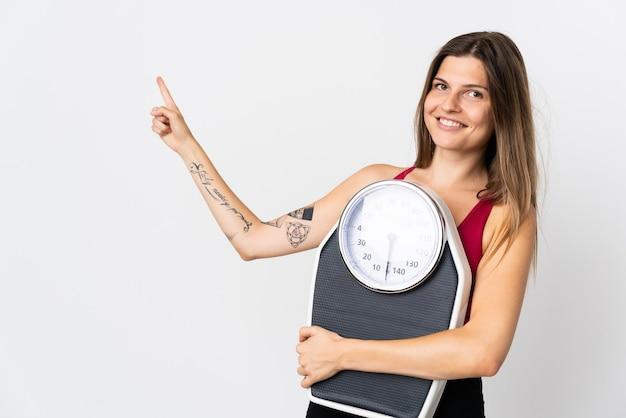 Jonge slowaakse vrouw geïsoleerd op wit met weegmachine en wijzende kant